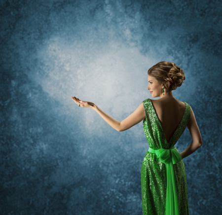 Woman in Green Dress Showing Empty Hand Elegant Model in Rich Gown Display Jewelry over Blue background Back Rear view