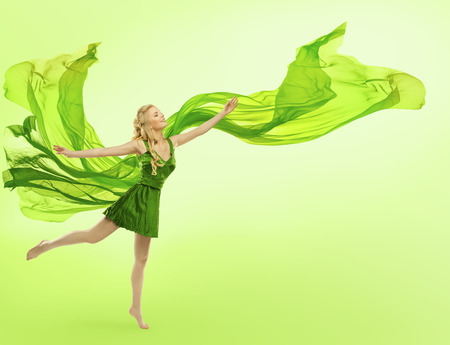 dress blowing in the wind: Woman in Green Dress with Blowing Cloth on Wind, Young Girl Posing Open Hands, Silk Fabric Fly over Green Background