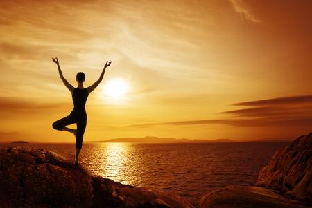 Yoga Meditación Concepto, silueta de la mujer meditando en la naturaleza, vista femenino Volver en la costa de piedra mirando al mar puesta de sol Foto de archivo