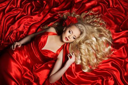 fantasy makeup: Mujer estilo de pelo de moda, Modelo de pelo largo rizado, que miente en color rojo de tela Foto de archivo