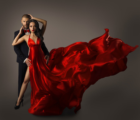 stunning: Fashion Couple Portrait, Woman Red Dress, Man in Suit, Long Waving Cloth Flying over Gray Background Stock Photo