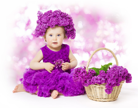 Baby Girl Lilac Flowers, Little Kid in Flower Crown Hat, Child and Bouquet Basket Stock Photo