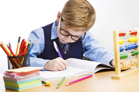 School Kid Writing, Student Child Learn in Classroom, Young Boy in Glasses Write, Education. Stock Photo