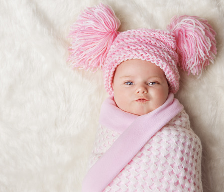 girl face close up: Baby Girl Wrapped Up in Newborn Blanket, New Born Kid Bundled Hat, One Month on Carpet Stock Photo
