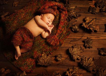 Baby slapen op herfst achtergrond, New Born Kid Asleep in Bladeren, Pasgeboren Liggend op Bruin Hout, een maand Stockfoto