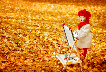 creative artist: Autumn Baby Artist Painting Fall Yellow Leaves, Creative Kid Girl Drawing Inspiration Stock Photo