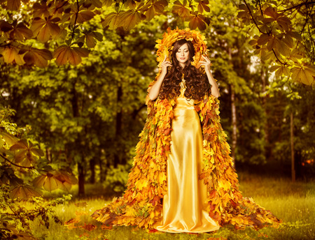 Autumn Fairy Woman in Forest, Nymph in Yellow Leaves Dress, Fantasy Goddess of Earth photo