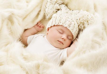 乳幼児: 新生児の子供生まれた帽子、新しい睡眠 1 ヶ月女の子のベッドで眠っている赤ちゃん 写真素材