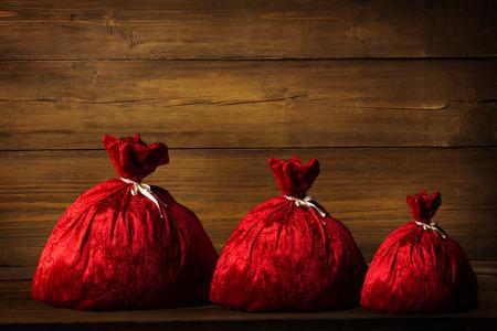sackful: Christmas Family Santa Claus Bags, Xmas Red Sackful on Brown Wood Plank Wall Background