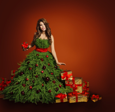 baubles: Christmas Tree Fashion Woman Dress, Model Presents Gift Boxes, Girl on Red Background, New Year Concept