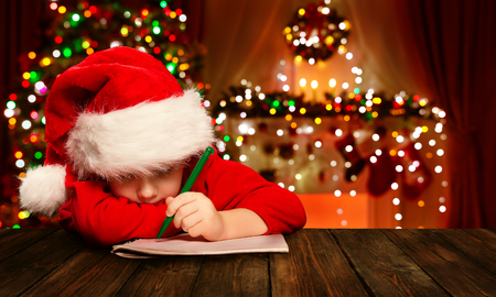 wish: Christmas Child Write Letter to Santa Claus, Kid in Santa Hat Writing Wish List, unfocused lights background