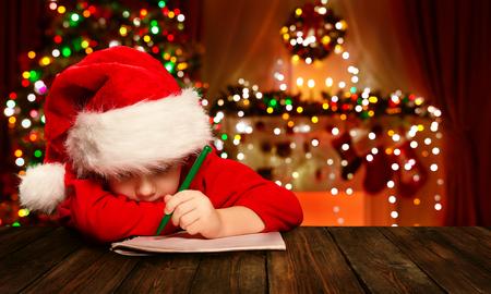 Natal Criança Escrever Carta ao Papai Noel, Kid no chapéu de Santa escrita lista de desejos, luzes desfocadas fundo