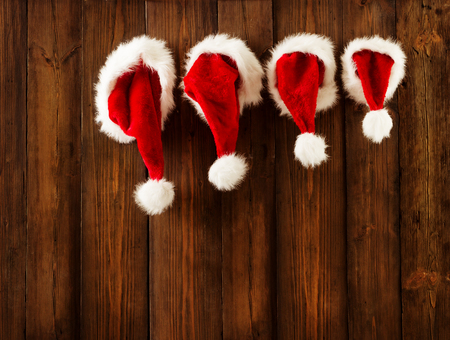 christmas: Christmas Family Santa Claus Hats Hanging on Wood Wall, Xmas Kid Hat Hang on Decorated Background Stock Photo