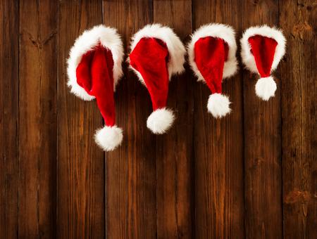 família: Natal da família de chapéus de Papai Noel que pendura na parede de madeira, Xmas Kid chapéu cair no fundo Decorado Banco de Imagens