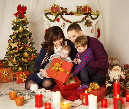 Christmas Family Open Present Gift Box, Mother Father and Baby Child in Decorated Room photo
