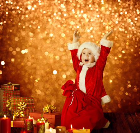 christmas fun: Christmas Kid, Happy Child Presents Gifts and Red Santa Bag, Boy Arms up, Golden Xmas Lights