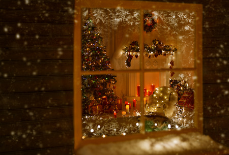 Christmas Window Holiday Home Lights, Room Decorated By Xmas Tree Candles Presents Gift, New Year Night, Snow And Frost Stock Photo