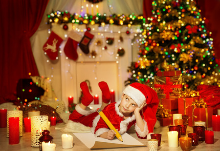christmas fairy: Christmas Kid Write Wish List, Child in Santa Claus Hat Writing Letter, Boy in Holiday Room