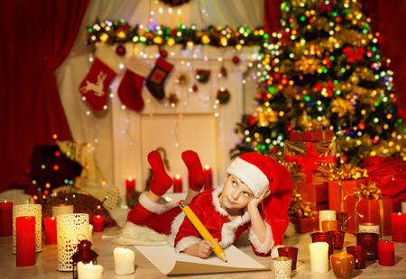 Kerstmis Kid schrijven Wish List, Kind in Santa Claus Hat Writing Letter, Jongen in Holiday Room Stockfoto