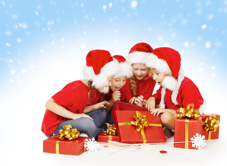 Christmas Children Open Presents, Kids in Santa Hat, Group of Girls and Boys Looking Gifts Toys Archivio Fotografico