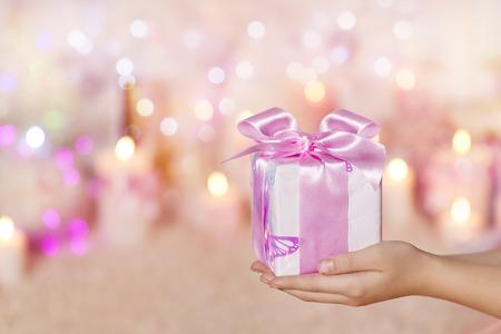 navidad elegante: Cajas de regalo en las manos, Dar presente rosado de seda arco de la cinta para la niña o mujer Foto de archivo