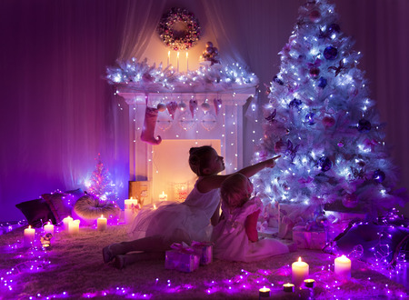 christmas tree presents: Christmas Night Room Kids under Lights Tree, Children Girls Looking Presents Gifts in Decorated Home Stock Photo