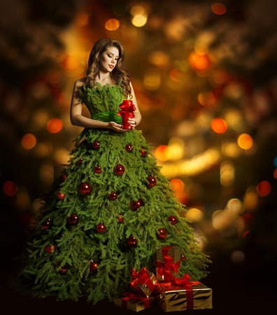 fashion: Christmas Tree Woman Fashion Dress, Model Girl and Candle, Present Gift on Xmas Red Lights Background Stock Photo