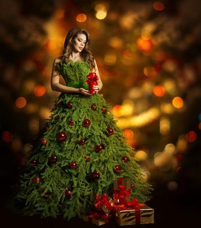 Kerstboom Vrouw Fashion Dress, Model Meisje en Kaars, Present Gift op Kerstmis rode lichten achtergrond