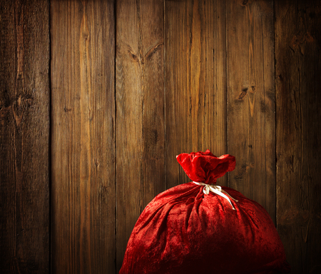 sackful: Christmas Santa Claus Red Bag Full, Xmas Wood Wall Background, Wooden Board Plank Texture Stock Photo