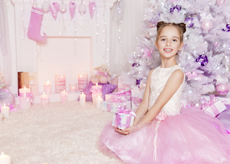the girl in stockings: Christmas Child Girl with Present Gift, Kid in Decorated Pink Interior with Xmas Tree