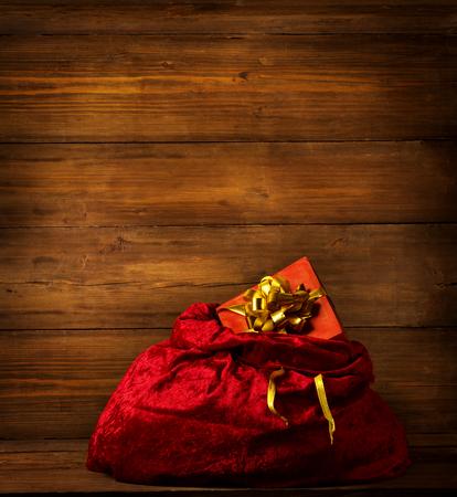 sackful: Santa Claus Bag, Christmas Red Sackful on Brown Wooden Background, Full Xmas Present Gift Box Toys