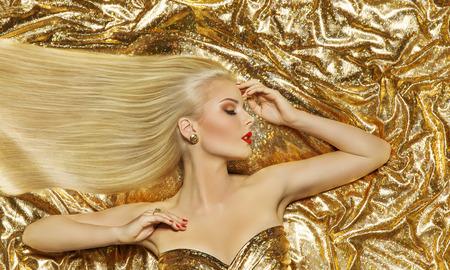 donne eleganti: Hair Style, Modella, Moda lunghi capelli dritti, Donna Sdraiato sul Panno Colore Oro