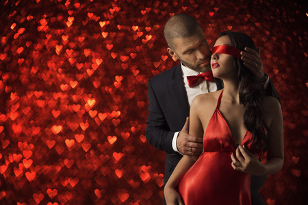 Sexy Couple Love, Man in Suit Undress Woman Blindfold, Red Heart Romance Foto de archivo