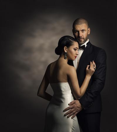 donna ricca: Coppia in abito nero e abito bianco, uomo ricco e Moda Donna Archivio Fotografico
