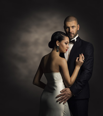 Pareja en Traje Negro y vestido blanco, hombre rico y Moda Mujer Foto de archivo