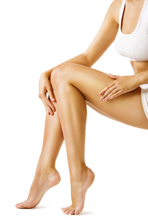 de rodillas: Las piernas de la mujer la belleza del cuerpo, Modelo sienta en blanco, el tacto de la piel de la pierna Foto de archivo