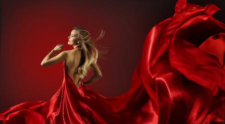 anochecer: Mujer en vestido de baile rojo, Modelo de manera con el paño del vuelo de la tela