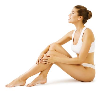 Žena Body Beauty Model dívka sedí v bílé prádlo, dotýkat pokožky nohou
