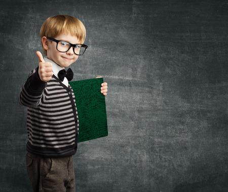profesiones: Niño de edad escolar en Gafas Pulgar hacia arriba, Kid Boy certificado retenido libro, educación exitosa Foto de archivo