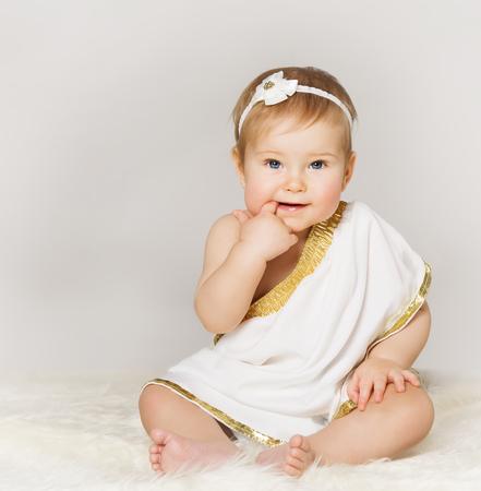 Meisje van de baby vinger in de mond, Kid Peuter in witte klederen zitten over grijze achtergrond