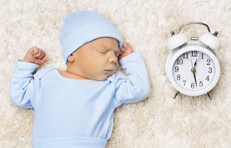 despertarse: El dormir recién nacido del bebé y reloj, recién nacido duerma en la cama Foto de archivo