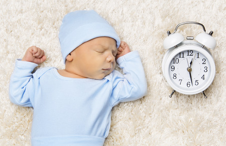 Slaap Pasgeboren baby en klok, New Born in bed slapen Stockfoto