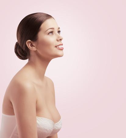 beaux seins: Femme Beauté Visage, fille Regarder ailleurs, Soins de la peau du sein, Chignon Banque d'images