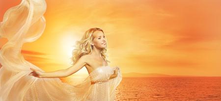 anochecer: Retrato mujer de belleza en Sun Lights, Chica Modelo de manera con el mantón de seda, la puesta del sol en el mar Foto de archivo