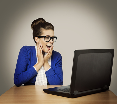Woman on Laptop, Happy Girl in Glasses with Notebook Looking to Screen over Gray background