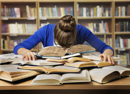 Student Studying Hard Exam and Sleeping on Books, Tired Girl Read Difficult Book in Library Archivio Fotografico