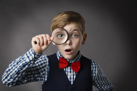 sorprendido: Niño considera a través de la lupa, Kid Ojo que mira con la lupa de la lente, Fondo gris