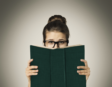 hands behind head: Open Book Hiding Face, Woman Eyes Reading in Glasses on Gray Background