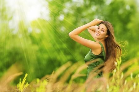 La mujer feliz, hermosa Muchacha activa libre en el fondo verde del verano al aire libre