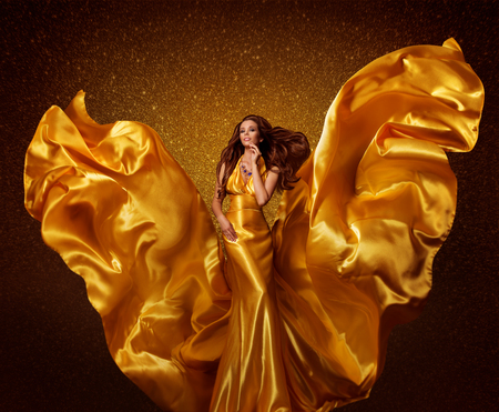 fluttering: Gold Fashion Model Woman, Silk Fabric Flying as Wings on Wind